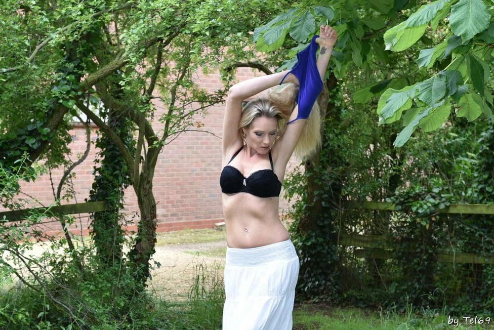 Blonde MILF Angel strips in the garden